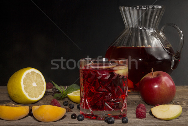 Stock photo: Compot in glass jug on old wooden table.