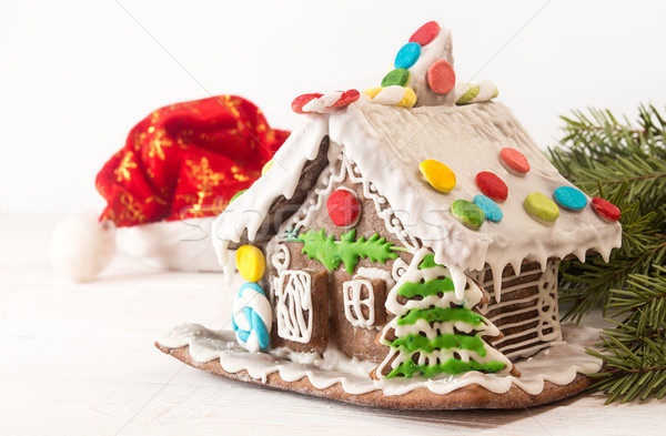 Stock photo: Christmas gingerbread house, hat Santa Claus on white