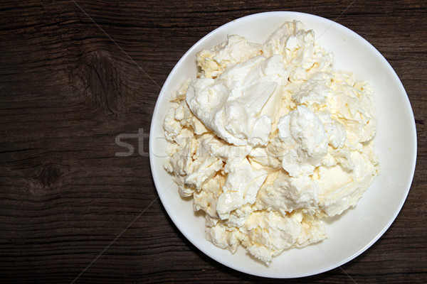 Cottage cheese in white plate on wooden table.  Stock photo © user_11056481