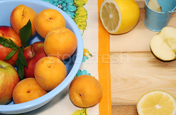 Apricots and apples in blue plastic bowl on wooden table. Stock photo © user_11056481