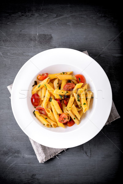 Penne with anchovy and tomato on a wooden surface. Stock photo © user_11224430