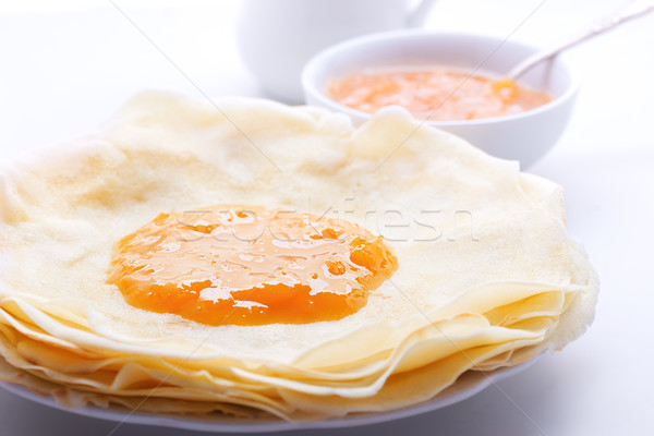 Crispy crepes with apricot jam served on a table. Stock photo © user_11224430