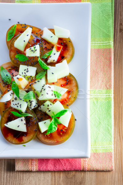 Tomato salad with melon, cheese, basil, sesame Stock photo © user_11224430