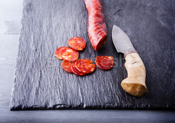 Spanish chorizo with a knife on a stone plate. Stock photo © user_11224430