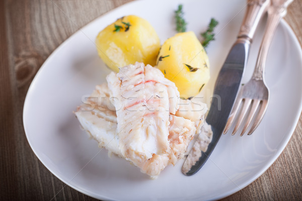 Steamed fish and potato on a plate served on plate. Stock photo © user_11224430