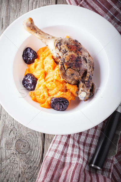Stock photo: Roasted duck leg with mashed carrot and dried prunes