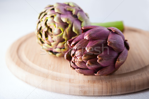 Two artichokes lying on a wooden plate Stock photo © user_11224430