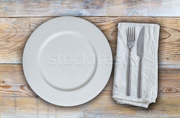 Empty plate with cutlery on untreated wood background Stock photo © user_9870494