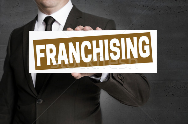 Franchising sign is held by businessman Stock photo © user_9870494