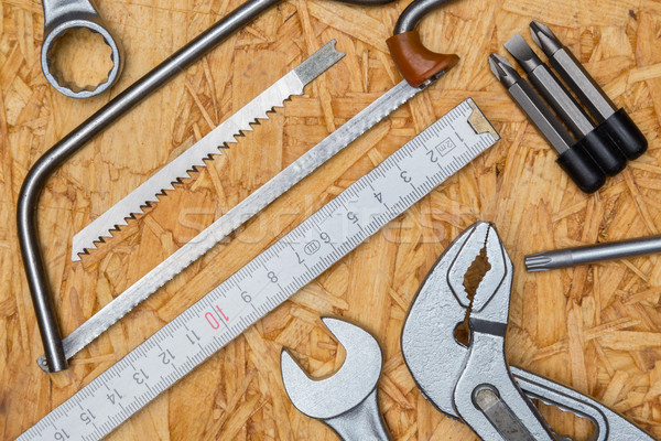 Tool concept, pliers, tine, saw, wrench on wooden plate and bird Stock photo © user_9870494