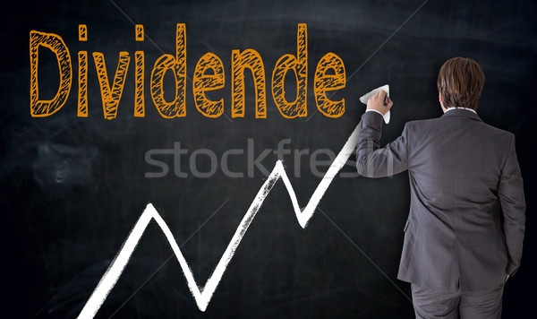 Businessman writes Dividende (in german dividend) on blackboard  Stock photo © user_9870494