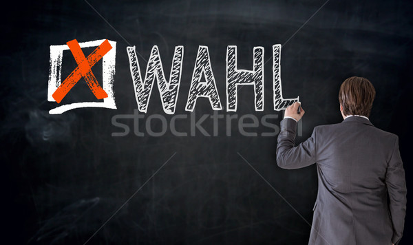 Businessman writes Wahl (in german Vote) on blackboard concept Stock photo © user_9870494