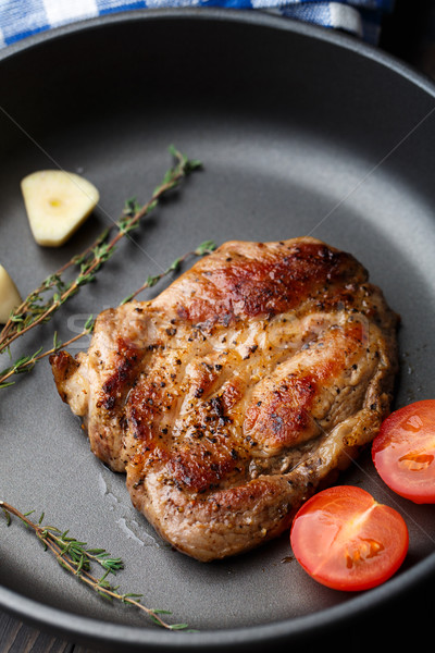 Steak with thyme, tomato and garlic. Stock photo © vankad