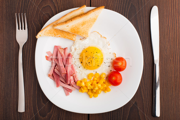 Fried egg with toasts, ham and cherry tomato Stock photo © vankad