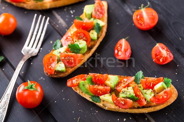 брускетта томатный авокадо травы черный деревянный стол Сток-фото © vankad