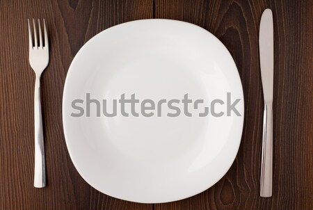 White empty plate, knife and fork served on table Stock photo © vankad
