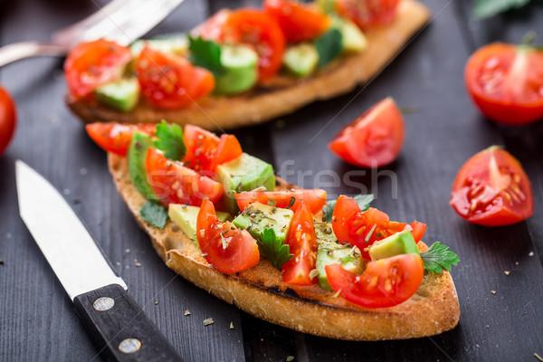 Сток-фото: брускетта · томатный · авокадо · травы · черный · деревянный · стол