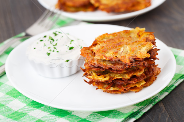Potato pancakes with sour cream Stock photo © vankad