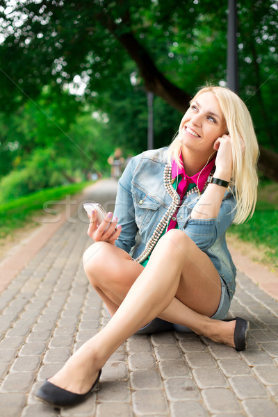 Stock photo: Young blond girl listening music