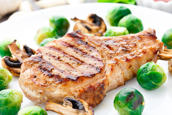 Grilled pork chop with brussels sprouts Stock photo © vankad