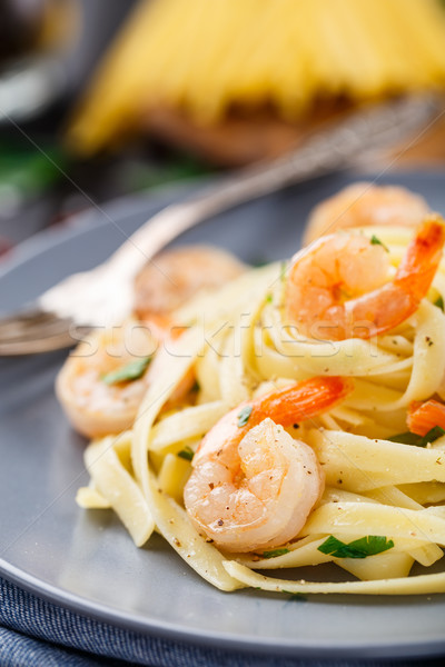 Tagliatelle with shrimps and parsley Stock photo © vankad