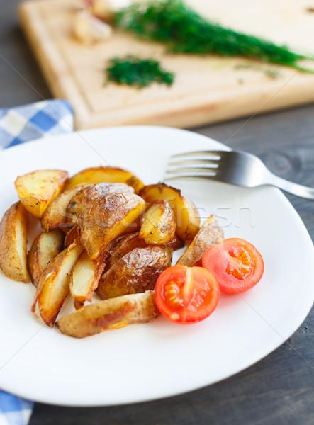 Fried potato wedges with cherry tomato Stock photo © vankad