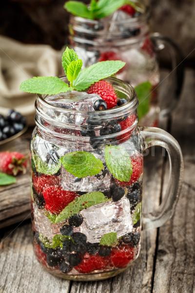 Detox drink with fresh berries in glass jars Stock photo © vankad