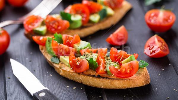 Bruschetta domates avokado otlar siyah ahşap masa Stok fotoğraf © vankad