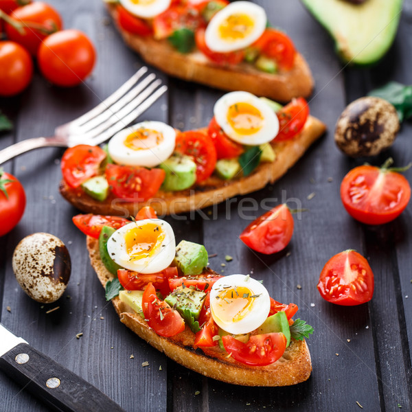 Bruschetta with tomato, avocado and quail egg Stock photo © vankad