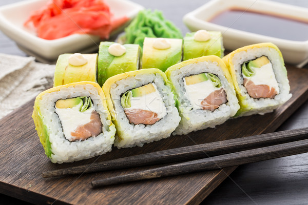Sushi roll covered with avocado Stock photo © vankad