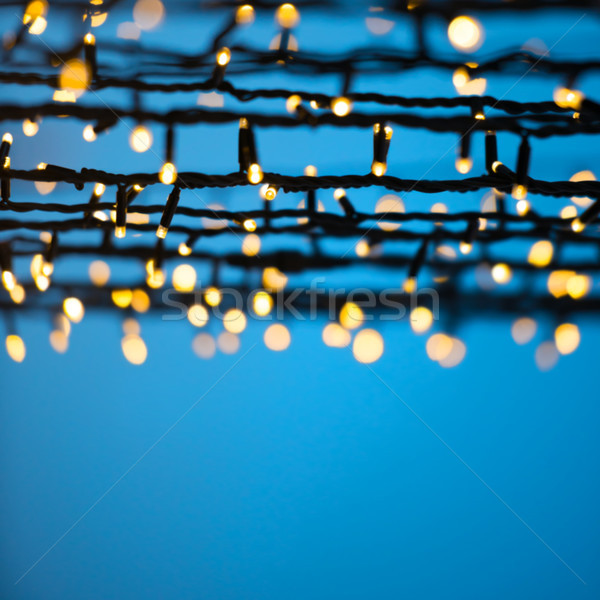 Stock photo: Christmas lights over blue night sky