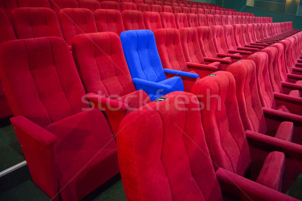 Blue chair between rows of red seats Stock photo © vapi
