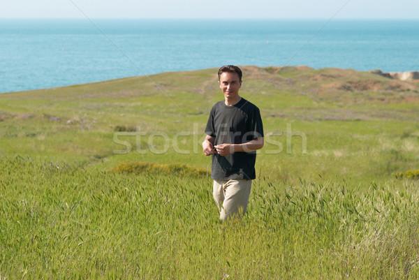 Młody człowiek pole trawy Błękitne niebo uśmiech człowiek szczęśliwy Zdjęcia stock © vapi