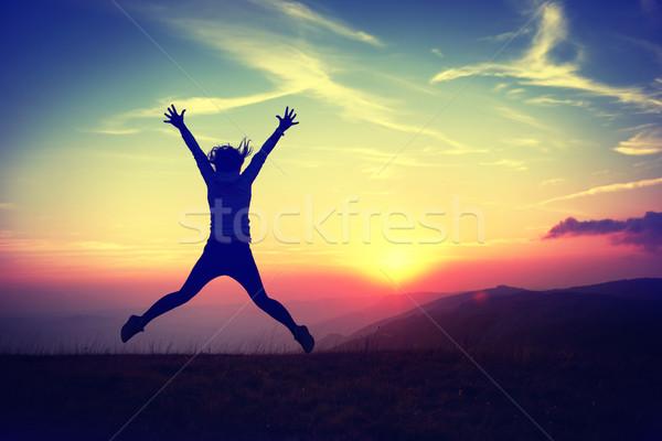 Fiatal nő naplemente sziluett ugrik kék ég ahogy Stock fotó © vapi