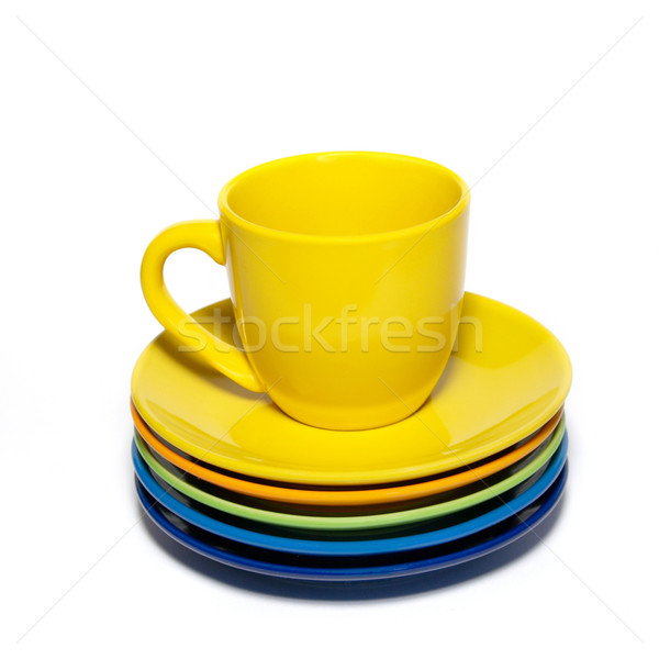 Yellow teacup and stack of saucers isolated on white. Stock photo © vapi