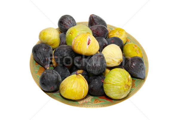 Stack of black and yellow figs on the plate isolated on white. Stock photo © vapi