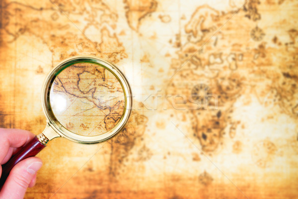 Old map and magnifying glass in a hand Stock photo © vapi