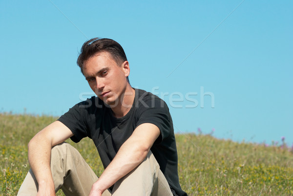 Young man sitting on the grass field Stock photo © vapi