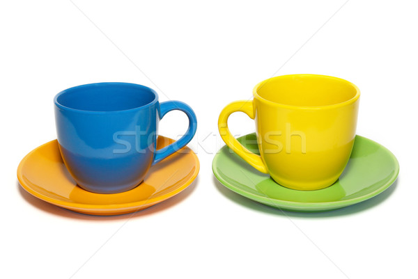 Stock photo: Colored teacups and saucers isolated on white.