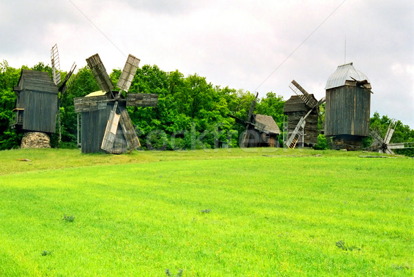Wooden mills on the field of green grass. Stock photo © vapi