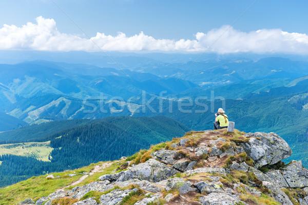 Mulher jovem sessão penhasco olhando montanha paisagem Foto stock © vapi