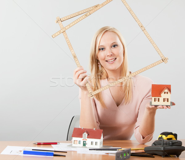 Stock photo: architect woman holding meter frame and exposing small house