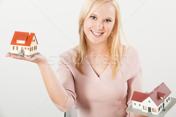 Stock photo: young woman balancing two houses with hands