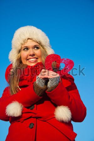 woman in red coat holding heart shape and sending a kiss Stock photo © varlyte