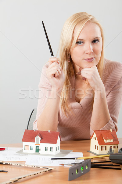 Stock photo: woman architect at her work table exposing house