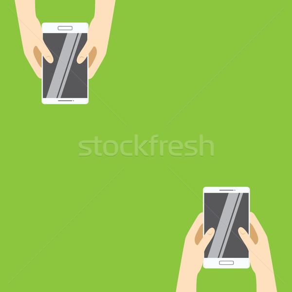 Hands holding white smartphones on a green background. Vector illustration in flat design.  Stock photo © vasilixa