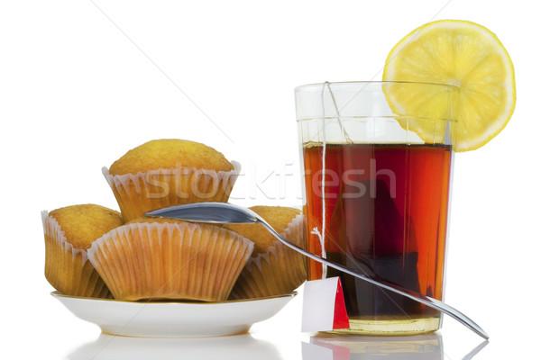 Glass with tea, a lemon and chocolate fruitcakes Stock photo © vavlt
