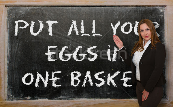 Teacher showing Put all your eggs in one basket on blackboard Stock photo © vepar5