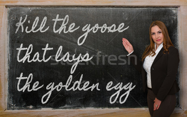 Teacher showing Kill the goose that lays the golden egg on black Stock photo © vepar5