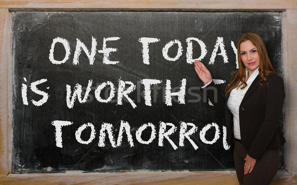 Teacher showing One today is worth two tomorrow on blackboard Stock photo © vepar5